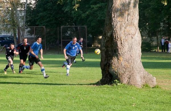 Jugadores corren tras el balón en un partido de fútbol con el roble de Orissaare como espectador. Foto: Irina Mägi